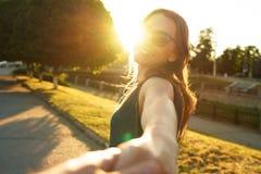 Podąża ja ręka w rękę - szczęśliwa młodej kobiety ciągnięcia faceta ` s ręka - Obraz Royalty Free