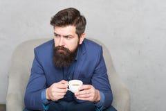 Podładowywa i przeładowywa M??czyzny biznesmena chwyta przystojny brodaty fili?anka kawy poj?cia stary kawa si? wzi?? interesy il zdjęcia stock