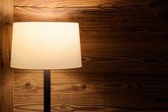 Podłogowa lampa przeciw drewnianej ścianie zdjęcia stock