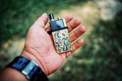 """New Vape pod system for quitting smoking habit alternative on hands. POD or """"ultra-portable systems"""" are essentially the middle-ground between your royalty free stock photos"""
