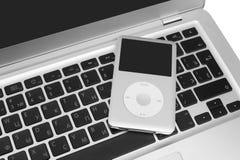Pod classic 160 Gb on silver laptop. Pavlograd, Ukraine - December 4, 2014: iPod classic 160 Gb on silver metal laptop. Studio shot, isolated on white background Stock Photo