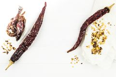 Pod dry chilli and pepper seeds. On a white wooden table royalty free stock image