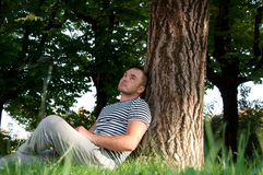 Pod drzewem mężczyzna obsiadanie Fotografia Stock