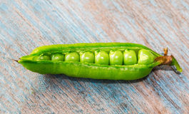 Pod of green peas. Green pea pod on an old wooden table, close-up Royalty Free Stock Photo