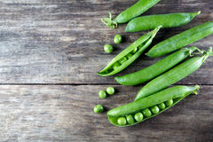 Pod of green peas on wood Stock Photo