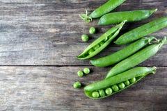 Pod of green peas on wood stock photo