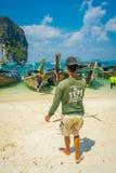 PODA,泰国- 2018年2月09日:长尾巴小船室外看法连续在与本地人的岸在Poda海岛上 免版税库存照片