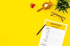 Podaniowa forma dla adoptuje dziecka na żółtym tło odgórnego widoku egzaminie próbnym w górę fotografia royalty free