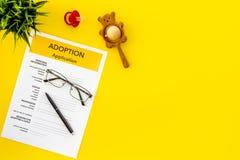 Podaniowa forma dla adoptuje dziecka na żółtym tło odgórnego widoku egzaminie próbnym w górę fotografia stock