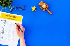 Podaniowa forma dla adoptuje dziecka na błękitnym tło odgórnego widoku egzaminie próbnym w górę obraz royalty free