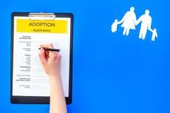 Podaniowa forma dla adoptuje dziecka na błękitnym tło odgórnego widoku egzaminie próbnym w górę zdjęcie royalty free