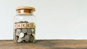 Podatku druku tekst na drewnianym kwadratowym bloku na pieniądze monecie zdjęcie stock