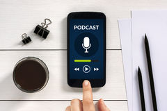 Podcast concept on smart phone screen with office objects. On white wooden table. All screen content is designed by me. Flat lay royalty free stock photography