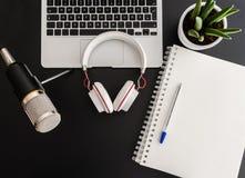 Podcast inspelningbegrepp med anteckna utrustning för ljudsignal på den mörka tabellen royaltyfri bild