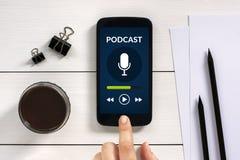 Podcast le concept sur l'écran intelligent de téléphone avec des objets de bureau Photographie stock libre de droits