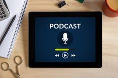 Podcast o conceito na tela da tabuleta com objetos do escritório em d de madeira foto de stock