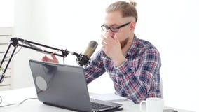 Podcasting, ροή και ραδιο έννοια ραδιοφωνικής αναμετάδοσης Νεαρός άνδρας στον υπολογιστή με ένα μικρόφωνο στο στούντιο ή απόθεμα βίντεο