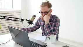 Podcasting, ροή και ραδιο έννοια ραδιοφωνικής αναμετάδοσης Νεαρός άνδρας στον υπολογιστή με ένα μικρόφωνο στο στούντιο ή φιλμ μικρού μήκους