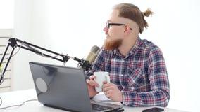 Podcasting, het stromen en radio het uitzenden concept Jonge mens bij de computer met een microfoon in de studio of bij stock video