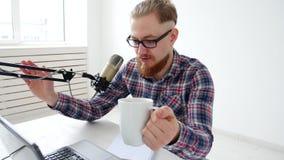 Podcasting, het stromen en radio het uitzenden concept Jonge mens bij de computer met een microfoon in de studio of bij stock videobeelden