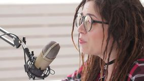Podcasting and radio concept. Radio host young woman in the studio in front of a microphone