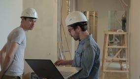 Podczas napraw architektów szkła pokazują klienta projekt na laptopie zbiory wideo
