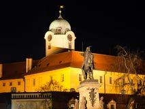 Podebrady por noche Estatua de Jiri z Podebrad con el castillo en el fondo, República Checa imagen de archivo