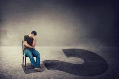 Podejmowanie decyzji i ?y? pytania jako rozwa?ny niespokojny m??czyzna, posadzony na krze?le w ciemnym pokoju, chwyt r?ka czo?o k zdjęcie stock