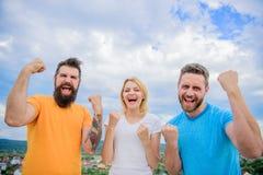 Podemos hacerla Celebre el éxito Maneras de construir al equipo acertado Soporte del Threesome feliz con los puños aumentados Com imagen de archivo libre de regalías