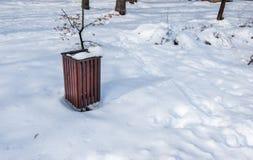 Poder de madera de la basura o de los desperdicios para la basura en el parque cubierto con nieve en la estación del invierno par imágenes de archivo libres de regalías