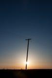 Poder poste silueteado en pradera canadiense en la salida del sol C vertical fotografía de archivo