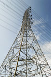 Poder y línea eléctrica de alto voltaje con el cielo azul foto de archivo