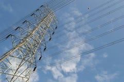 Poder y línea eléctrica de alto voltaje con el cielo azul fotos de archivo
