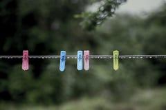 Podeszczowej wody kij na clothespin i clothesline spojrzeniu koliduje ponieważ clothesline i clothespin używamy dla suchego odzie Zdjęcia Stock