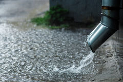 Podeszczowej wody spływanie od metalu downspout podczas powodzi pojęcie ochrona przeciw ulewnym deszczom zdjęcia royalty free