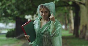 Podeszczowy dzień na parc działającej młodej kobiecie trzyma niektóre mapy i jest ubranym deszczowa zbiory wideo