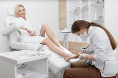 Podiatrist που κάνει τη διαδικασία για το πόδι πελατών Στοκ εικόνα με δικαίωμα ελεύθερης χρήσης