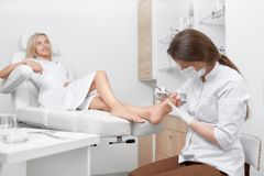 Podiatrist doctor cleaning foot from callus. Podiatrist doctor making procedure for clients feet with special long iron tool, cleaning from callus. Pretty stock images