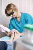 Podiatrist doing a foot laser treatment Royalty Free Stock Photography
