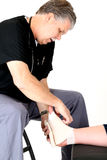 Podiatrist in scrubs wrapping a girls ankle Stock Photography