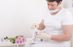 Podiatrist at work. Podiatrist ( chiropodist ) with a surgical mask at work , using nail polish Stock Photo
