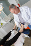 Podiatrist working in clinic. Podiatrist working in a clinic Stock Images