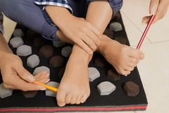 Podiatry clinic. Little boy on massage mat doing exercises for flatfoot prevention.Child flatfoot treatment using special massage carpet.Foot strengthening Stock Image