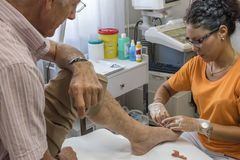 Podiatry. Doctor curing an elderly patient feet Royalty Free Stock Photography