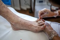 Podiatry. Doctor curing an elderly patient feet Royalty Free Stock Photo