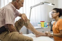 Podiatry. Doctor curing an elderly patient feet Royalty Free Stock Image