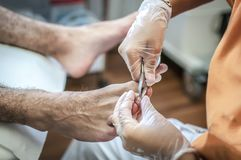 Podiatry. Doctor curing an elderly patient feet Royalty Free Stock Photos