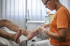 Podiatry. Doctor curing an elderly patient feet Royalty Free Stock Images