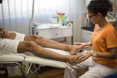 Podiatry. Doctor curing a young patient feet Royalty Free Stock Photography
