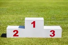 Podio di legno bianco del vincitore disposto sul campo di sport dell'erba verde sopra immagini stock libere da diritti